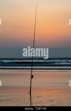 Silhouette of fishing rod at the edge of the Atlantic Ocean at sunset from Agadir beach, Morocco, Africa - Stock Image