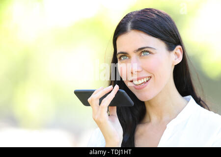 Adult woman using voice recognition on smart phone in a park - Stock Image