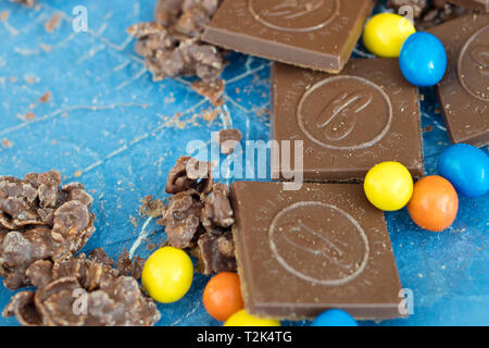 Several chocolate sweets on blue background. - Stock Image