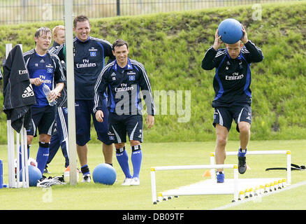 HSV Hamburg player David Jarolim (R) jumps over obstacles on the pitch holding a medicine ball, while teammates - Stock Image