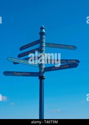 A signpost in Whitby showing distances sailed in Nautical Miles to places discovered by the famous navigator Captain James Cook - Stock Image