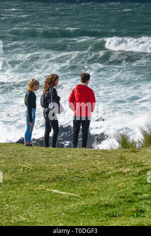 Young people standing on the rugged coastline at Little Fistral in Newquay in Cornwall. - Stock Image