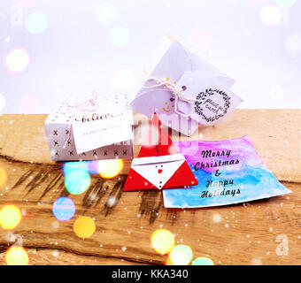 Christmas decoration on a wooden table with square gift box and greeting card for celebration with snow falling - Stock Image