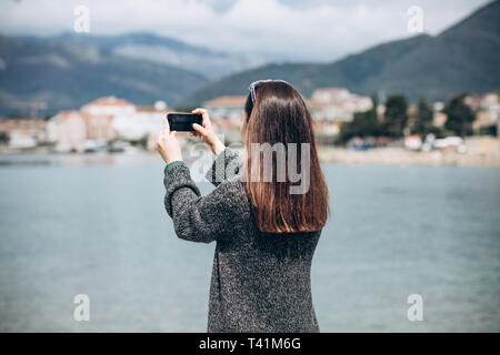 A girl or a tourist photographs a beautiful view of the sea and the urban architecture of the small coastal town of Tivat in Montenegro. - Stock Image