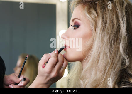 Make-up artist working in make-up studio, applying makeup on face of female clients. Makeup artist applies lipstick brush. Evening make-up. Close-up - Stock Image