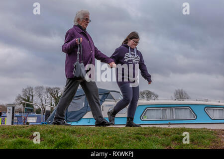 Young girl with Downs Syndrome with her Grandmother walking at White Mills Marina, Earls Barton, Northamptonshire, uk. - Stock Image