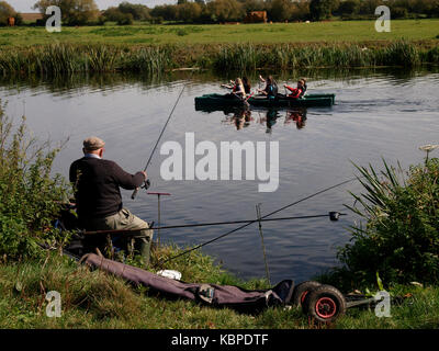 Old man fishing on the River Avon with kayakers paddling past, Tewkesbury, Gloucestershire, UK - Stock Image