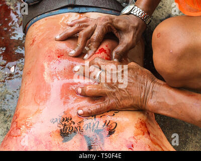Navotas City, Philippines. 4th Jan, 2012. (EDITOR'S NOTE: IMAGE HAS SOME GRAPHICS).A barangay tanod seen squeezing the wound caused by flagellation to avoid infection during Good Friday. Credit: Josefiel Rivera/SOPA Images/ZUMA Wire/Alamy Live News - Stock Image