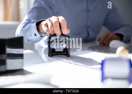 Close-up Of A Person's Hand Stamping With Approved Stamp On Document At Desk - Stock Image