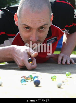 Crawley Sussex, UK. 19th Apr, 2019. Lloyd Evans from the Swansea Bay Packers competing in the World Marbles Championship held at The Greyhound pub at Tinsley Green near Crawley in Sussex . The annual event has been held on Good Friday every year since the 1930s and is open to players from around the world Credit: Simon Dack/Alamy Live News - Stock Image