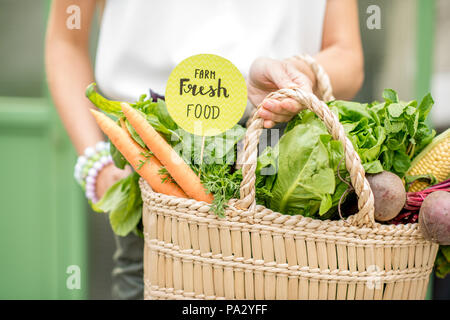 Holding bag full of fresh organic vegetables with green sticker from the local market on the green background - Stock Image