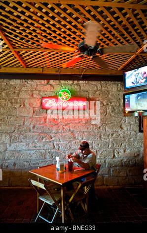 A Man Sitting Alone In    Auslander Biergarten Restaurant And Hill Country Fredericksburg, Texas, USA - Stock Image
