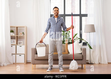 indian man with mop and bucket cleaning at home - Stock Image