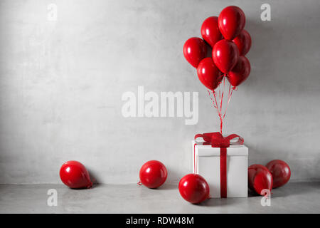 Red balloons and white gift box on concrete wall background - Stock Image