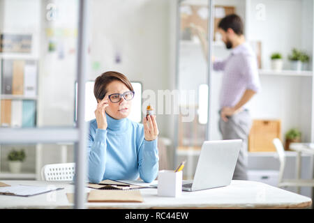 Young businesswoman with headache holding bottle with painkiller pills and reading instruction on label - Stock Image