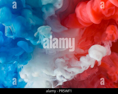 Blue, white and red paint in water.  Colors of the flag of The Netherlands and of France. The photograph could also be used in a vertical way. - Stock Image