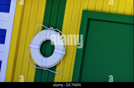 A stock image of a beach house with a life preserver. - Stock Image