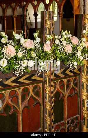UK, Cornwall, Trebetherick, Daymer Bay, Saint Enodoc's Church, wedding flowers decorating C15th Rood screen base - Stock Image