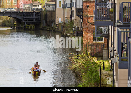 Three people in a canoe, enjoying a peaceful, warm spring evening on the river Wensum in Norwich UK. - Stock Image
