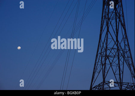 Electricity pylons and full moon - Stock Image