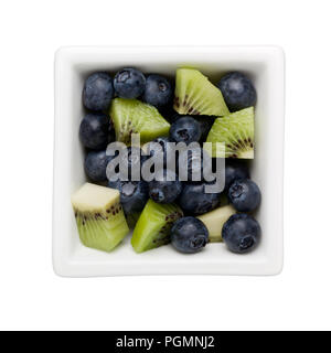 Blueberries and diced kiwifruit in a square bowl isolated on white background - Stock Image