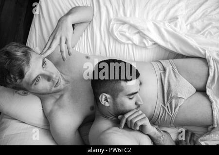 Handsome gay male couple in naked in bed with one thinking as his partner sleeps with his head on his stomach - Stock Image