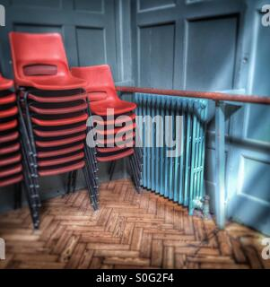 Red chairs stacked in an old blue hall, school/community concept. - Stock Image