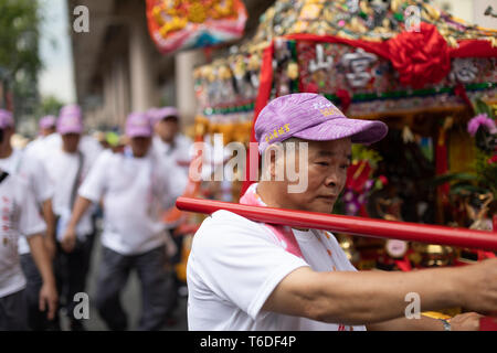 A man carries a palanquin with a Mazu statue during a local procession through the streets of Taipei. - Stock Image