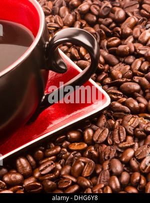 a flat pile group of roasted dark brown coffee beans with cup and saucer - Stock Image