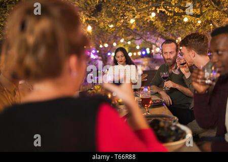 Friends drinking wine, enjoying dinner garden party - Stock Image