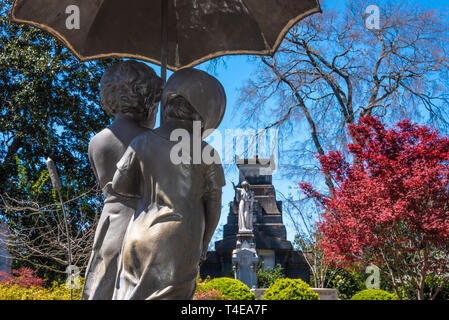 Cast iron bronze-finished sculpture, titled 'Out in the Rain,' of children under an umbrella at Historic Oakland Cemetery in Atlanta, Georgia. (USA) - Stock Image