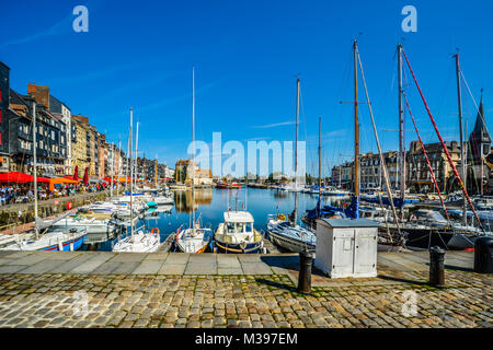 Boats, sailboats, slated covered homes and sidewalk cafes line the pier at the Normandy, Calvados fishing seaside - Stock Image