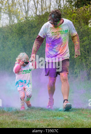 Father and his little girl covered in paint on Macmillan cancer charity 5K color fun run. - Stock Image