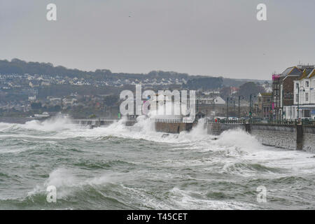 Penzance, Cornwall, UK. 14th April 2019. UK Weather.  The second week of the school holidays started with rain, strong easterly wind and big waves smashing into the seafront at Penzance today. Credit: Simon Maycock/Alamy Live News - Stock Image