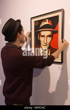London, UK. 28 August 2014.  Curator James Elphick straightens the screenprint picture 'Burroughs 100 Years' by Kate Simon and Shepard Fairey. The 'Animals in the Wall' exhibition showcases a new side to iconic American writer and creative mind Willam S Burroughs. The exhibition features 40 original Burroughs artworks and never before shown pieces of contributing artists. 'Animals in the Wall' is curated by James Elphick and Yuri Zumancic and runs from 29 August 20 to 7 September 2014 at the Londonewcastle Project Space in Redchurch Street, Spitalfields, London. - Stock Image