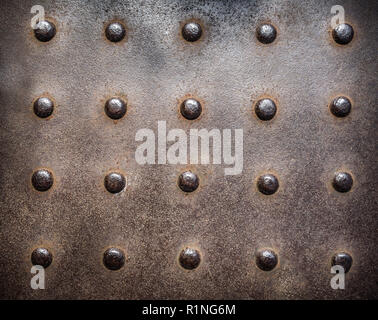 Rusty, studded cast iron vintage industrial plate background. - Stock Image
