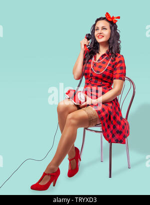 smiling young pinup woman in red dress and nylon stockings sitting on a chair and talking on phone over green background - Stock Image