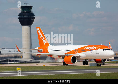 An Easyjet Airbus A320 NEO aircraft, registration G-UZHJ, taxying for take off in front of the control tower at Manchester Airport, England. - Stock Image