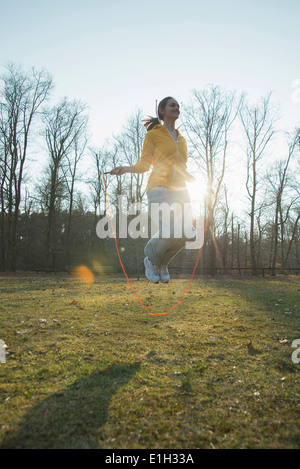 Young woman exercising in field with skipping ropes - Stock Image