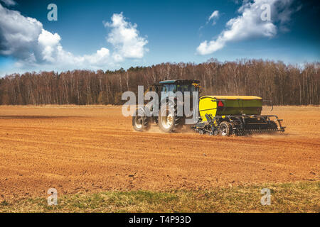 farming - farmer with tractor on the field seeding sowing crops in spring - Stock Image