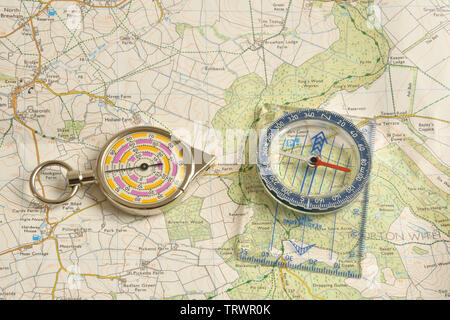 Compass and a wheeled map measuring device on a Ordnance Survey map. - Stock Image