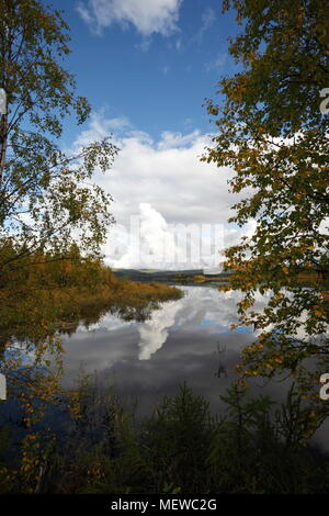 Cumulus clouds are towering over a lake in autumn. The forest on the shore is reflected in the still water. - Stock Image
