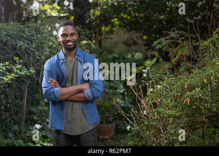 An African man standing in a garden, arms crossed - Stock Image