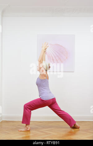 Senior woman with gray hair doing yoga exercises at home in front of a wall with a picture, asana warrior I - Stock Image
