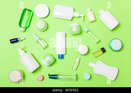 Group of plastic bodycare bottle Flat lay composition with cosmetic products on green background empty space for you design. Set of White Cosmetic con - Stock Image