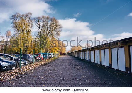 Footpath with fallen leaves along parked cars in a parking area and locked garages in Poznan, Poland - Stock Image