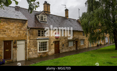 Cotswold limestone adorns the facade of these elegant terraced cottages in the picturesque market town high street of Chipping Campden-one is for sale - Stock Image