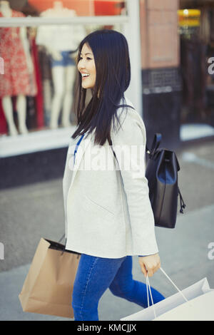 Smiling young woman walking along storefront with shopping bags - Stock Image