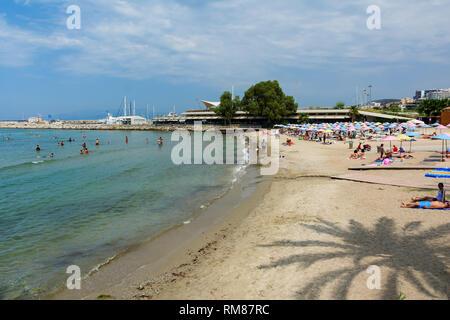 KUSADASI, TURKEY - AUGUST 20, 2017: Beautiful sand beach of Kusadasi with colorful straw umbrellas and lounge chairs, Aegean Sea,Turkey. - Stock Image