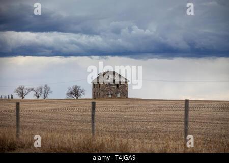 Prairie Storm Clouds in Saskatchewan Canada Stone House Abandoned - Stock Image